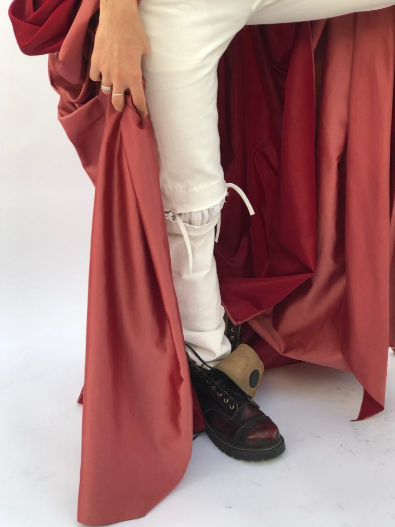 Androgynous white cotton boned corset and white denim ripped jeans.. Special Edition raspberry pink silk taffeta cloak with complex cartridge pleating at the back.