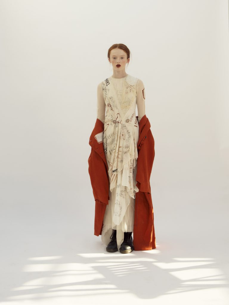 Elizabeth by Elizabeth Emanuel the Designer Special Edition Art asymmetrical organic cotton layered dress hand stamped and drawn. Mounted on cotton tulle with hand painted fabric buttons at the waist. Brick red asymmetrical linen coat with handmade silk and tulle label