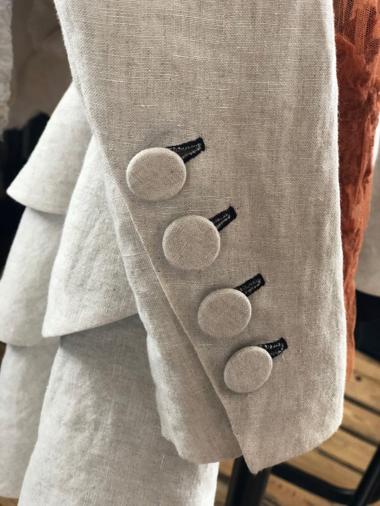 Ivory organic linen frock coat with matching buttons on the cuff.