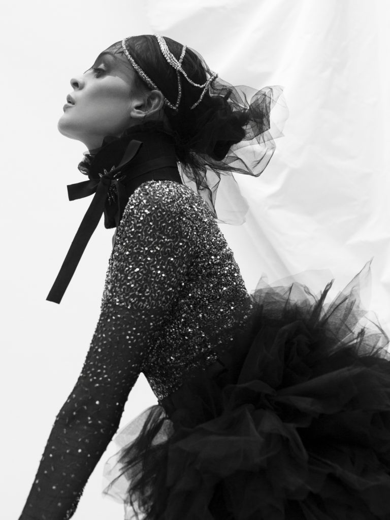 Elizabeth by Elizabeth Emanuel the Designer Hand embroidered crystal headdress on black tulle. Black structured cotton collar with black tie and hand made crystal star brooch. Silver sequin Red Carpet spangled black tulle cardigan