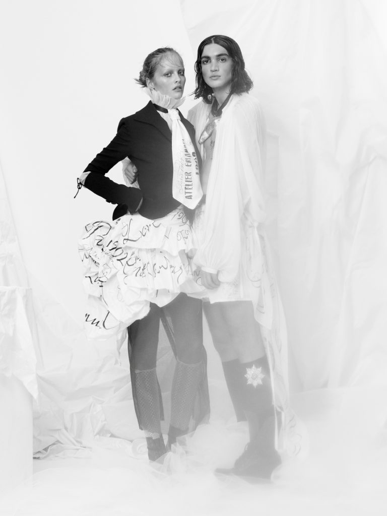 """Elizabeth by Elizabeth Emanuel the Designer She wears: Black silk moss crepe fitted jacket with """"medieval"""" slashed elbows with organic hand dyed cotton muslin insert. Special Edition. Artisan. White silk paper taffeta ruffled skirt with black handwritten text. Hand stamped and stencilled oversized tie at the neck in matching silk taffeta. Androgynous oversized Duelist shirt worn with hand stamped white cotton boxer shorts"""